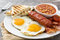 Traditional full English breakfast with fried eggs, sausages, beans, mushrooms, grilled tomatoes and bacon