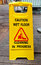 Caution wet floor sign cleaning in progress sign on wood floor