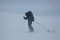 Ski touring man with sled in bad weather