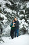Happy loving couple walking in snowy winter forest, spending christmas vacation together. Lifestyle capture.