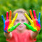 Little girl with hands painted in colorful paints ready for hand prints