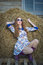 red-haired girl in a dress in the hay