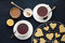 Sweet cookies in heart shape with two cups of tea, honey and lemon on dark blue background Valentines day.