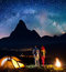 Pair tourists holding hands, standing near camp and enjoying beautiful starry sky and Milky way. Astrophotography