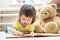 Child reading book for toy teddy bear, little girl learning and