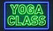 Yoga class neon sign on brick wall background.