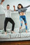 Young beautiful funny couple man woman in love having fun jumping from bed indoors at home