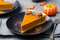 Pumpkin pie, tart made for Thanksgiving day on a black plate. Grey stone background.
