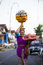Balinese woman with cild loads the offering of food in wooden jar on her head