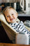 Cute smiling baby boy waiting mommy in high nursery chair