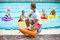 Lifeguard holding rescue can while children swimming in pool