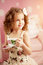 Little cute girl in a pink dress drinks tea with sweets in the c
