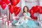 Cute baby girl celebrating birth day together close to red balloons.Lovely scene of baby on sofa divan with presents and