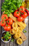 Pasta, vegetables, herbs and spices for Italian food on wooden background