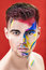 Portrait of young attractive man with colored face paint on red background. Professional Makeup Fashion. ffantasy art