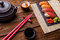 Sushi Set served on gray stone slate with soy sauce, grey teapot and cup of tea