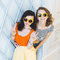 Beautiful young couple fashionable girls blonde and brunette in a bright yellow dress and sunglasses posing and smiling for the ca