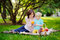 Beautiful little boy with his young mother having a picnic in summer sunny park