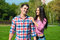 Young beautiful loving couple in checked shirts and jeans standing on the green lawn and laughing