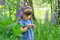 Little girl playing in sunny blooming forest. Toddler child picking lupine flowers. Kids play outdoors. Summer fun for family with
