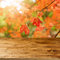 Empty wooden table over fall leaves background. An autumn season concept