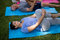 Smiling trainer exercising while lying down with senior people