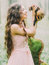 The happy woman with long curly hair in the light pink dress holding, petting and playing with the ferret in the green