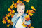 Portrait of funny cute smiling white Caucasian toddler child girl with blond hair lying on green grass with yellow autumn leaves