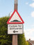 A traffic sign on a post outside humps for 200 yards direction p