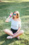 Young beautiful happy woman sitting on the grass in sunglasses