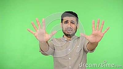 ¡No, por favor tengo miedo! Hombre con pánico levantando las palmas como para defenderse, asustado fondo verde, clave croma almacen de video