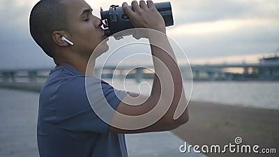 Água potável afro-americano do atleta durante o exercício de corrida video estoque
