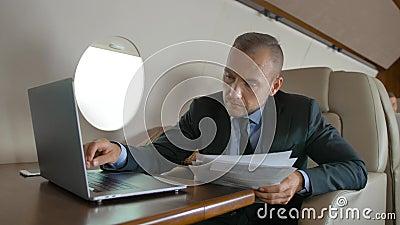与冲浪在私人喷气式飞机豪华内部的互联网里面的macbook的英俊的男性  股票视频