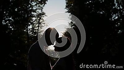 Älska kramar för ett par och kyssar mot bakgrunden av solnedgången, solskenpasserandeen till och med deras framsida lager videofilmer