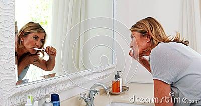 Ältere Frau, die ihre Zähne im Badezimmer putzt stock video