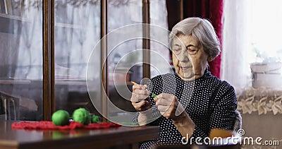 Ältere Frau sitzt und strickt stock video footage