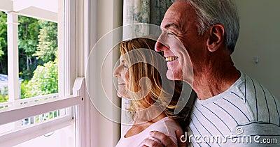 Ältere Paare, die auf einander beim vom Fenster heraus schauen einwirken stock video