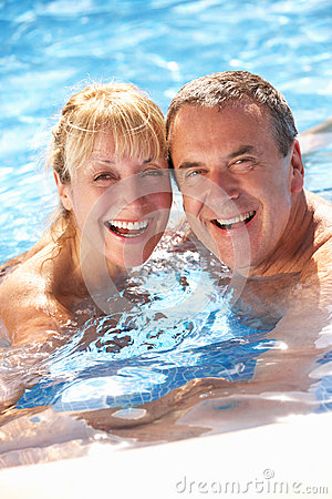 Ältere Paare, die Spaß im Swimmingpool haben