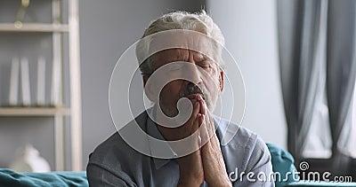 Ältere Senioralvater beten mit Hoffnung allein zu Hause stock footage