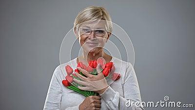 Ältere weibliche riechende Blumen und Lächeln auf Kamera, romantisches Geschenk, Weiblichkeit stock video