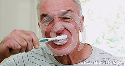 Älterer Mann, der seine Zähne im Badezimmer putzt stock video footage