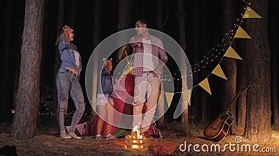 Älvande familj, mamma och dotter skrattar glatt och dansar runt eld i skogen under nattens picknick på semester stock video