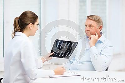 Ärztin mit dem alten Mann, der Röntgenstrahl betrachtet