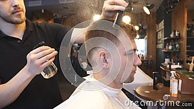 年轻在男性头发的发式专家喷洒的水从喷雾器在切开以后在理发店 梳他的头发的美发师 股票录像