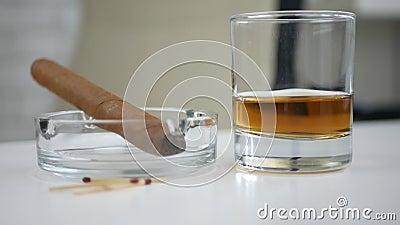在烟灰缸和一块玻璃的调味的黑抽烟的雪茄用在表上的威士忌酒 股票视频