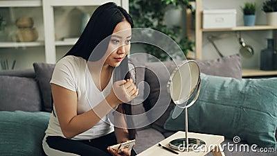 Ładna młoda dama wtedy muska jej włosy cieszyć się elegancki i patrzeje stawia na makijażu używać twarz proszek w lustrze zbiory wideo