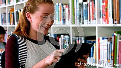 Écolière de sourire à l'aide du comprimé numérique dans la bibliothèque clips vidéos