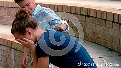 Écolier consolant son ami triste sur des étapes dans le campus banque de vidéos