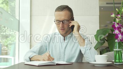 Écriture d'homme d'affaires dans le planificateur quotidien tout en parlant du téléphone portable clips vidéos