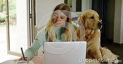 Écriture de femme sur le bloc-notes avec son chien à la maison 4k banque de vidéos